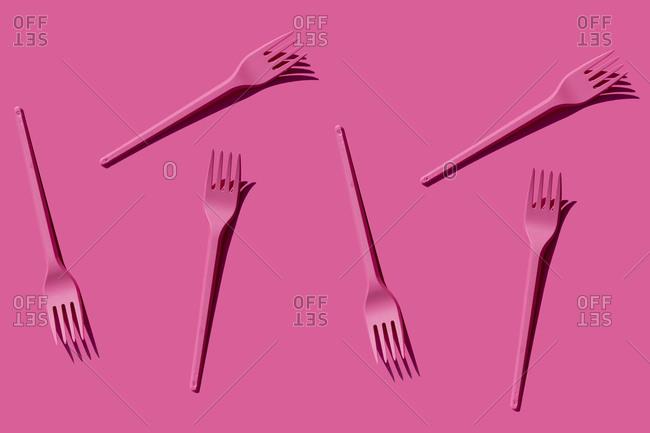 Pattern of pink plastic forks against pink background