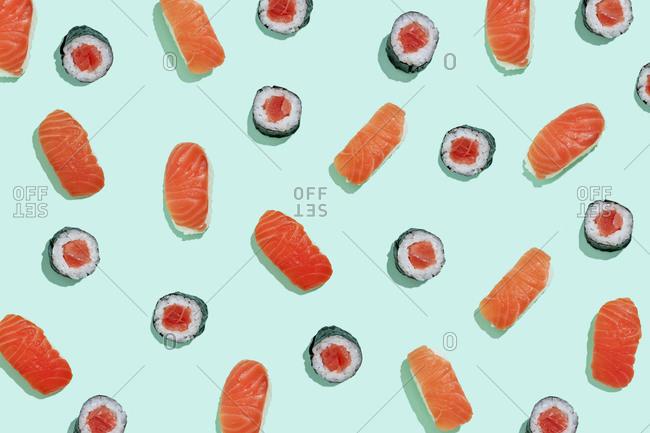 Salman sushi nigiri and maki pattern on mint green background