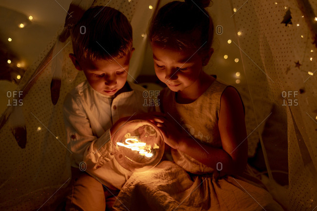 Sibling holding light while sitting in room during Christmas