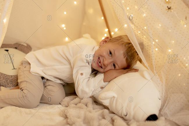 Cute little boy lying down on bed with teddy bear