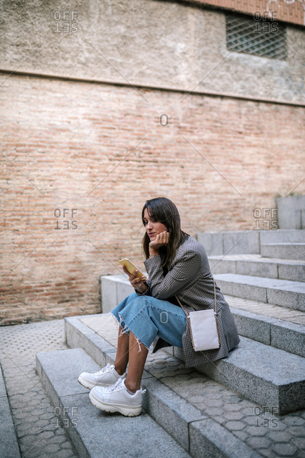 Young woman using smart phone with hand on chin while sitting on staircase in city