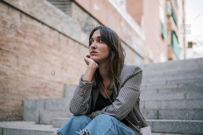 Thoughtful woman with hand on chin sitting outdoors