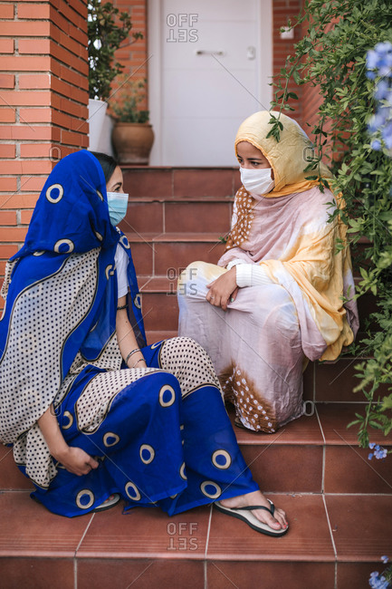 Friends wearing protective face mask looking at each other while sitting on staircase