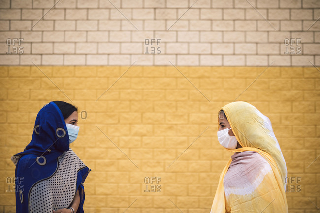 Female friends keeping social distancing while wearing face mask standing by wall