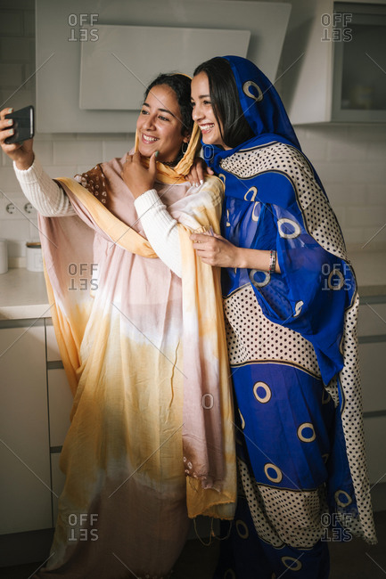 Young friends taking selfie on smart phone while standing in kitchen