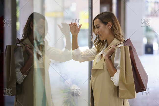 Woman with shopping bag standing while looking at shop window in city