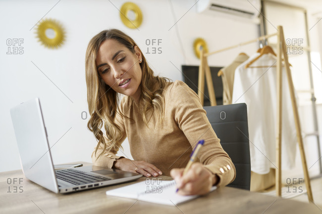 Businesswoman working while sitting by table at home