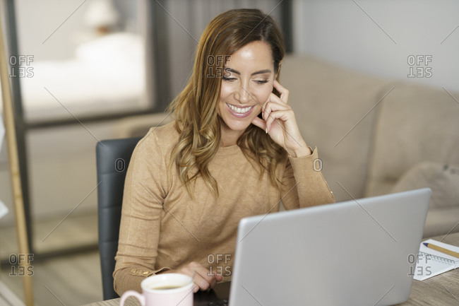 Businesswoman smiling while working on laptop at home