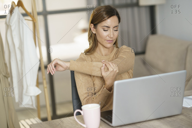 Businesswoman stretching hand while working on laptop at home