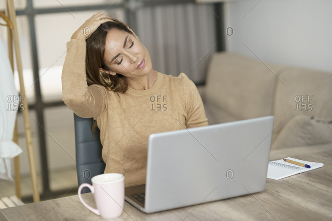Businesswoman doing neck exercise while working on laptop at home