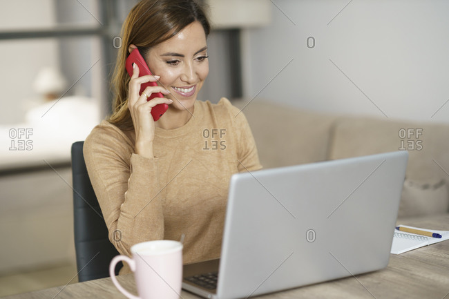 Smiling businesswoman talking on phone while working on laptop at home