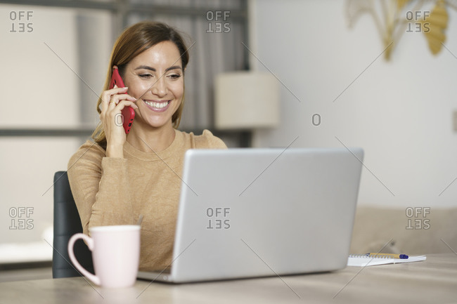 Businesswoman smiling while talking on phone at home