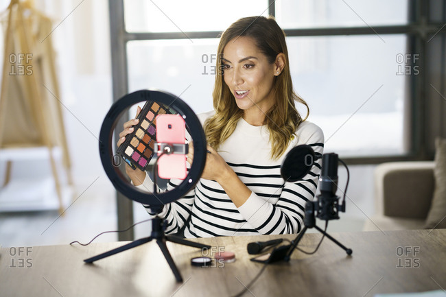 Beautician sitting and giving make-up tutorial on mobile phone at home