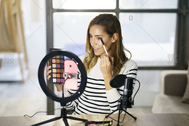 Woman sitting and giving make-up tutorial on mobile phone at home
