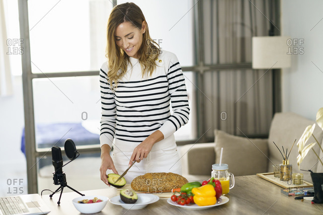 Nutritionist cutting fruit during online tutorial at home