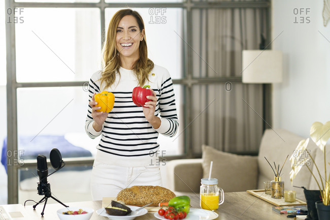Smiling woman showing vegetable during online tutorial while standing at home