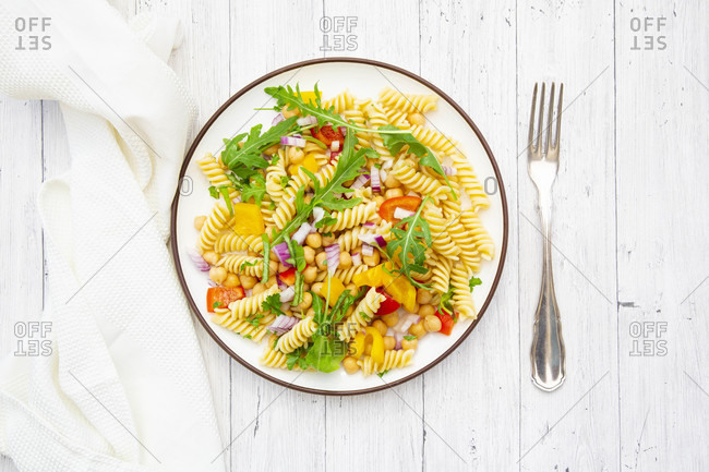 Plate of vegetarian pasta salad with chick-peas- bell pepper- arugula- onion- parsley and basil