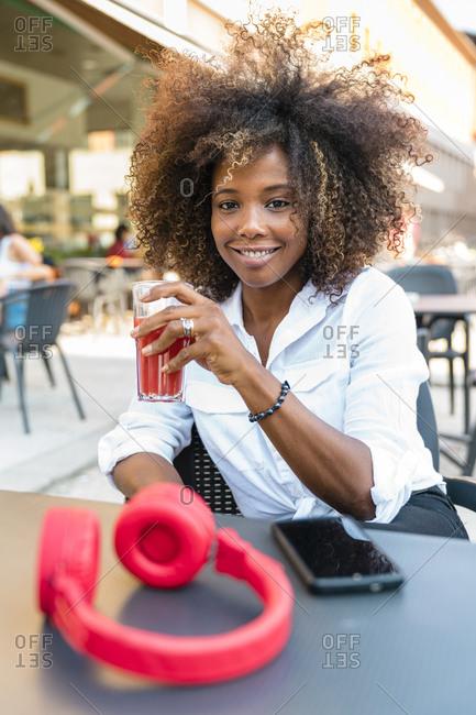 Woman drinking juice while sitting at sidewalk cafe