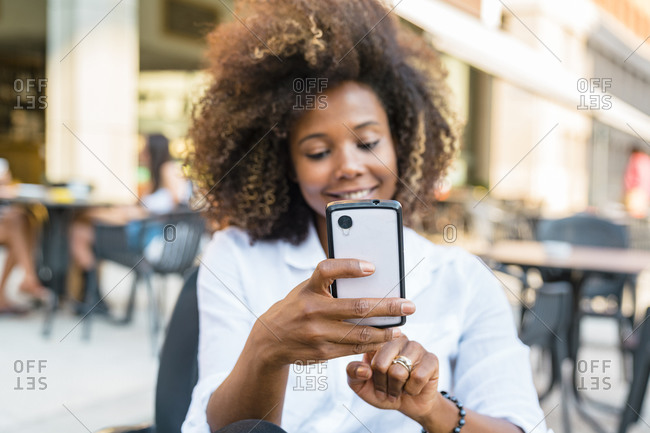 Woman taking selfie on smart phone while sitting at sidewalk cafe