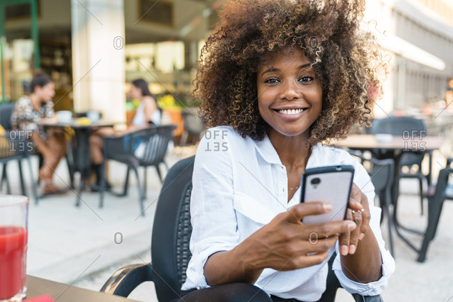 Woman text messaging on smart phone while sitting at cafe
