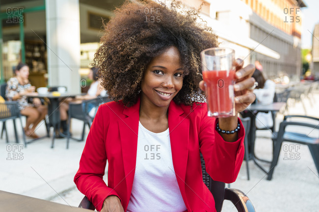 Mid adult woman holding juice glass while sitting at sidewalk cafe
