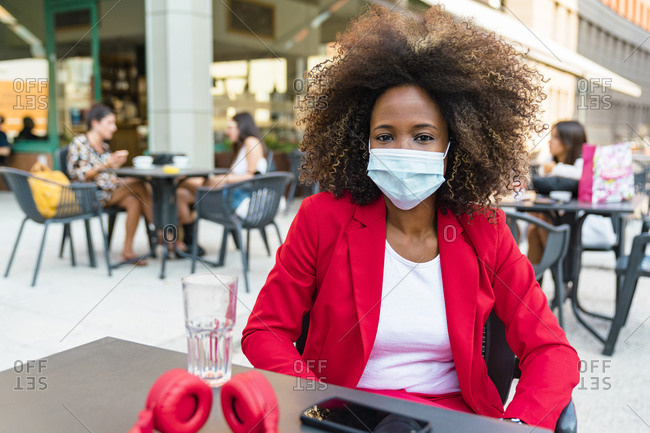 Woman wearing protective face mask sitting at sidewalk cafe