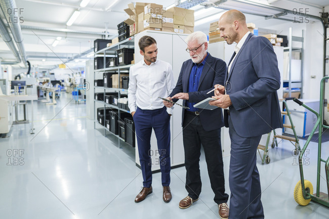 Senior manager discussing over machine part with male colleagues while standing at illuminated factory