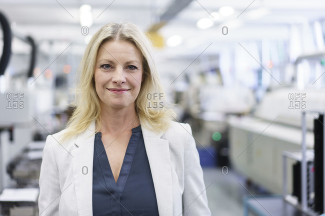 Smiling mature blond businesswoman in businesswear standing at illuminated industry