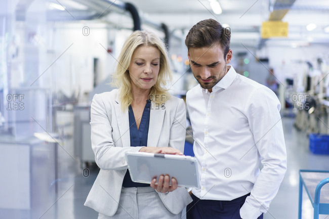 Confident blond businesswoman discussing over digital tablet with male colleague at factory