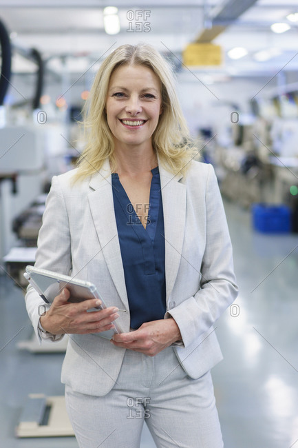 Smiling mature blond businesswoman holding digital tablet while standing at illuminated industry