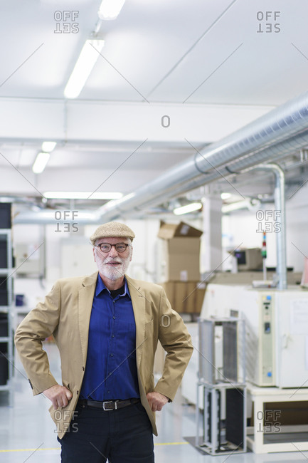 Confident senior businessman standing with hands on hip at factory