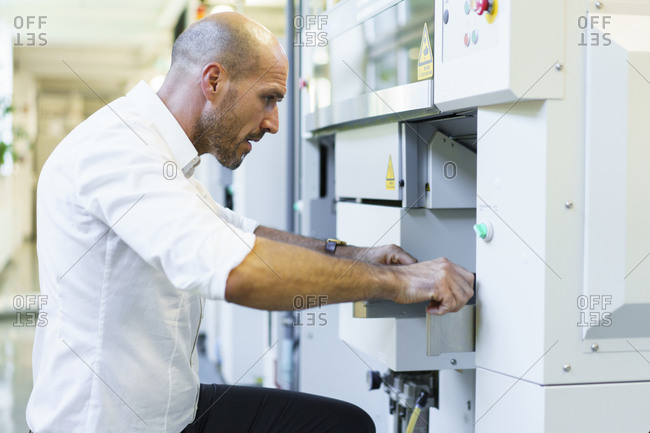 Mature male technician examining machinery at factory