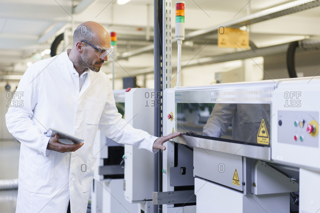 Mature male technician holding digital tablet examining machinery at factory
