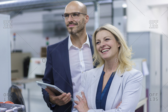 Cheerful businesswoman standing by colleague while looking away in factory