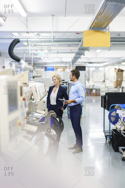 Young engineer discussing with mature businesswoman while standing by machinery at factory