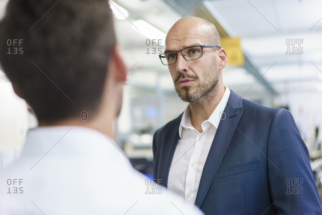Confident bald businessman looking at young male technician in factory