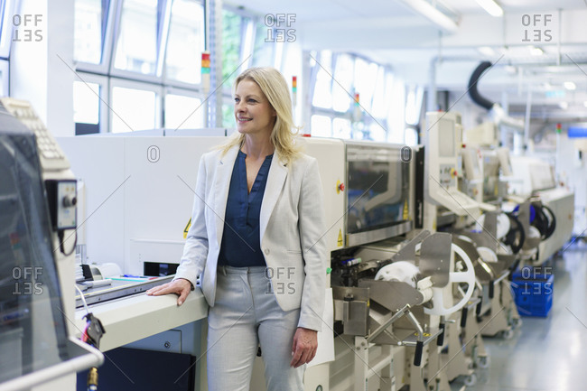 Thoughtful mature blond businesswoman standing by machinery while looking away at illuminated industry