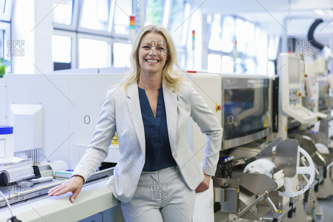 Smiling mature blond businesswoman standing by machinery at illuminated industry