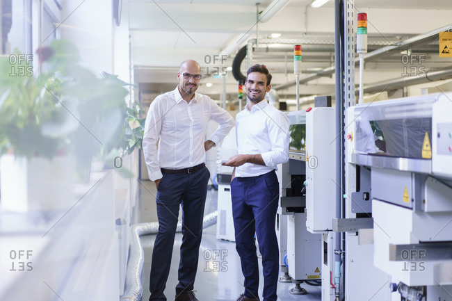 Smiling male engineers holding remote control while standing by machinery at factory