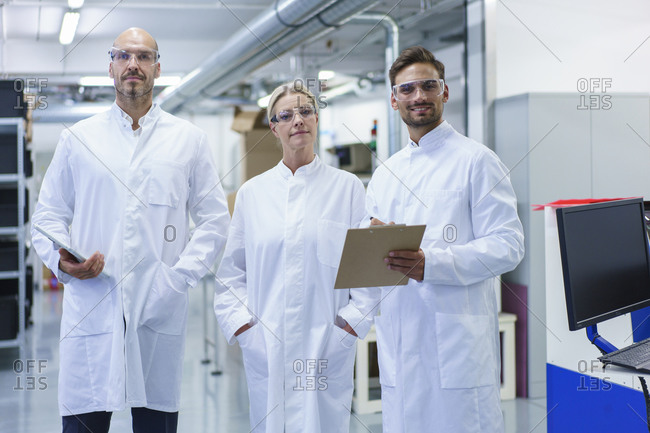 Confident male and female scientists standing in white lab coat at illuminated laboratory
