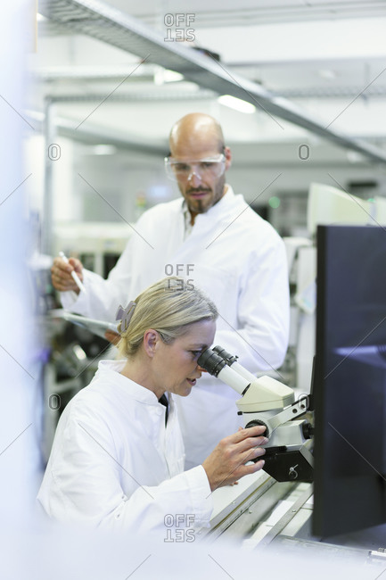 Female scientist doing research while looking into microscope by male colleague in laboratory