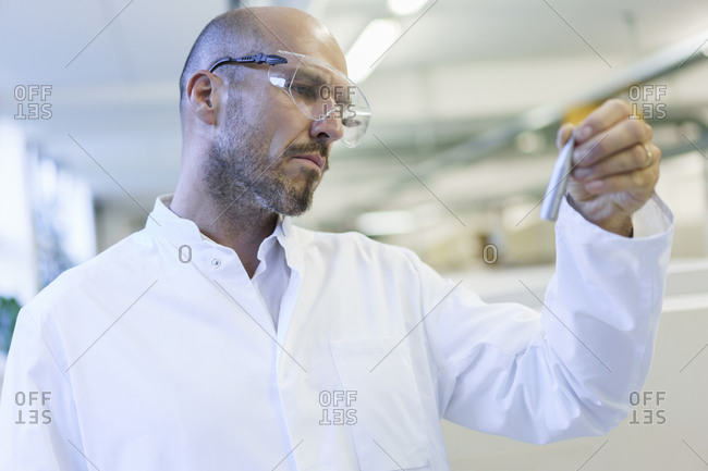 Mature male technician wearing protective eyewear looking at sample in factory