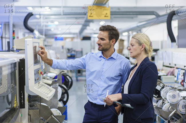 Mature businesswoman standing by young male technician using machinery at illuminated factory