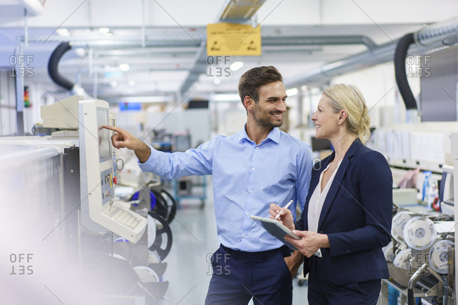 Smiling male technician looking at businesswoman while standing by machinery at illuminated factory