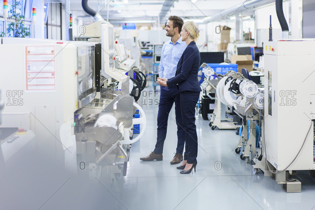 Businesswoman and businessman looking at machinery in illuminated industry