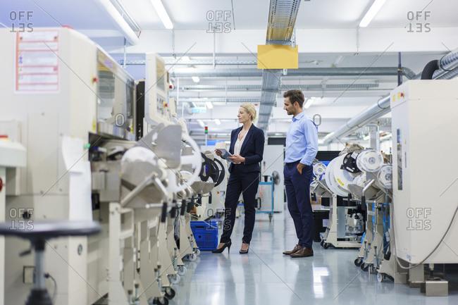 Male technician standing near businesswoman analyzing machinery at factory