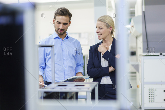 Businesswoman discussing with young male technician in illuminated factory