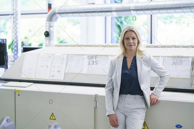 Confident blond businesswoman standing against machinery in illuminated factory