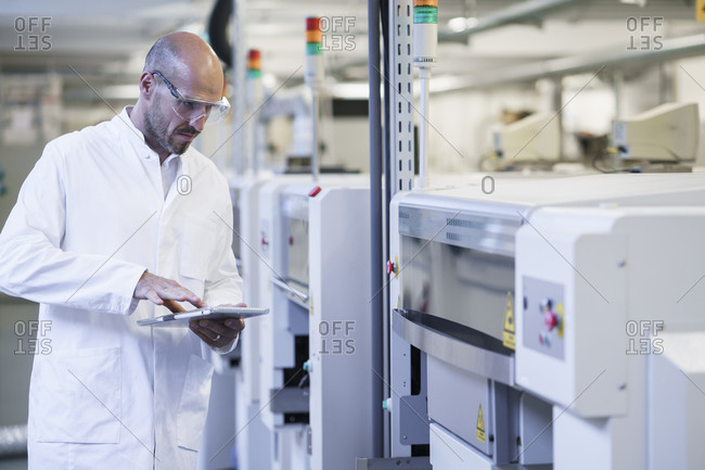 Mature male technician using digital tablet while examining machinery at laboratory