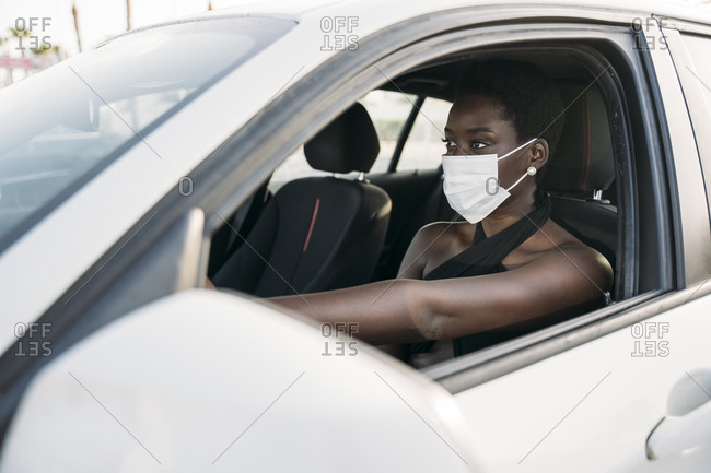 Young woman with face mask driving car